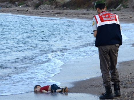 GRAPHIC CONTENT A Turkish police officer stands next to a migrant child's dead body off the shores in Bodrum, southern Turkey, on September 2, 2015 after a boat carrying refugees sank while reaching the Greek island of Kos. Thousands of refugees and migrants arrived in Athens on September 2, as Greek ministers held talks on the crisis, with Europe struggling to cope with the huge influx fleeing war and repression in the Middle East and Africa. AFP PHOTO / DOGAN NEWS AGENCY = TURKEY OUT =STR/AFP/Getty Images